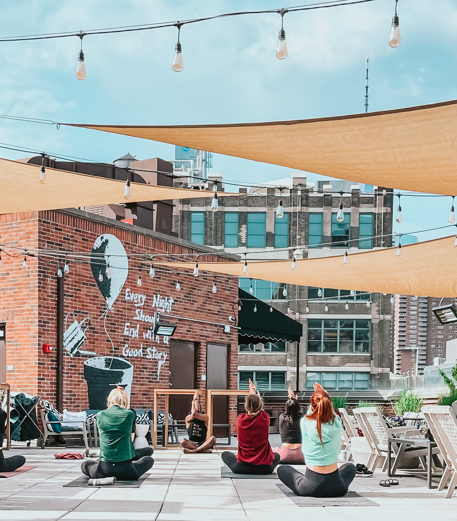 Arlo SoHo rooftop daytime with yellow fabric awnings and hanging string lights and several people seated on the floor on yoga mats stretching and background is a brick facade with a mural and a cityscape