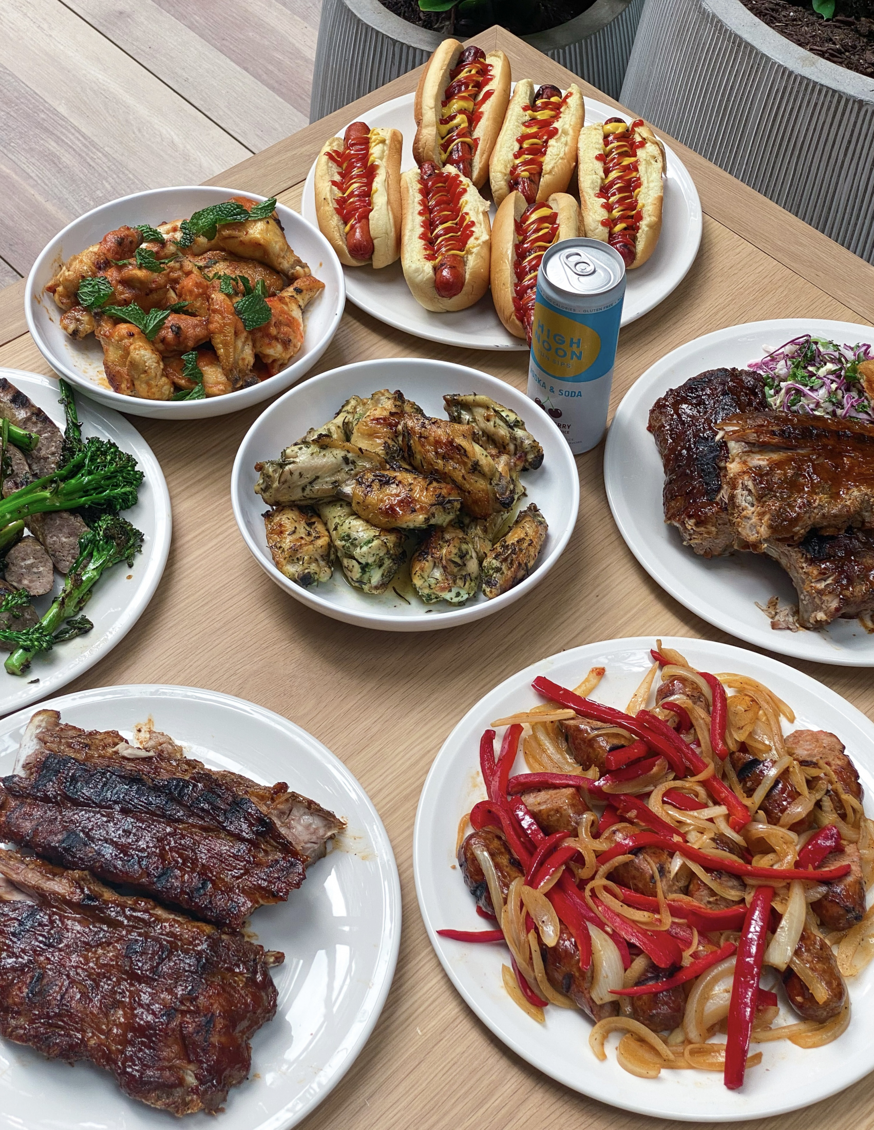 wooden table with plates of ribs and wings and hot dogs