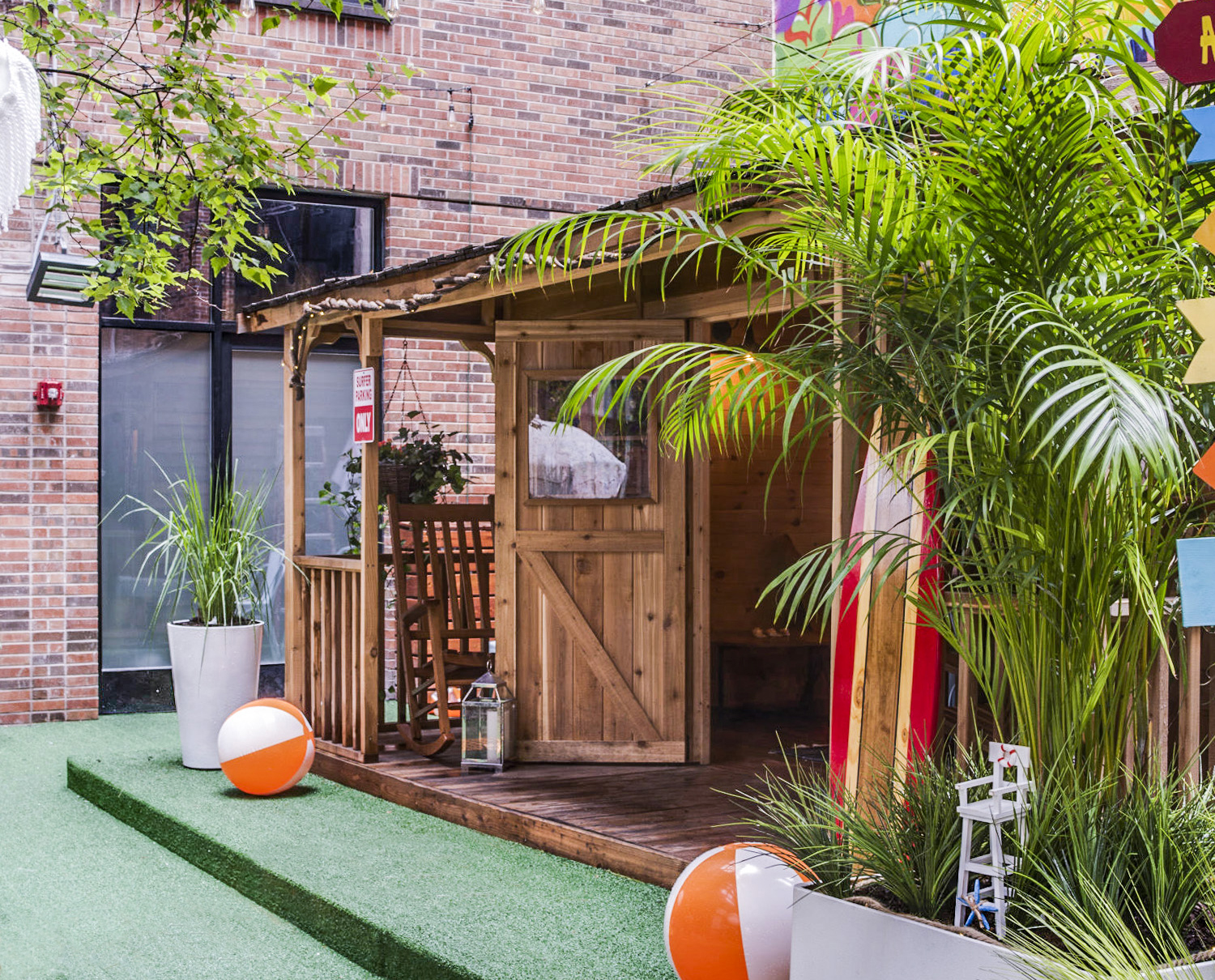 Cedar cabins in Arlo SoHo outdoor Courtyard with a red surfboard leaning on the right side of the cabin and ground is covered with green astroturf and green dune palm leaves to the right and orange and white beach balls