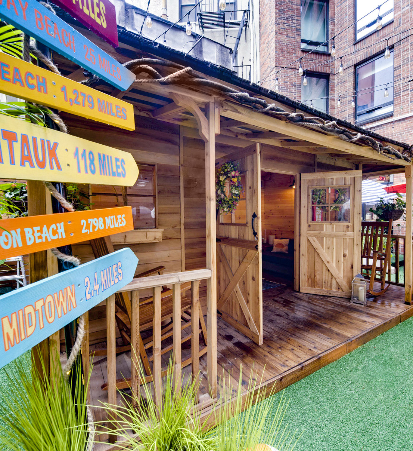 Cedar cabins in Arlo SoHo outdoor Courtyard with a bright multi color wooden sign post on the left indicating mileage to different beaches and ground is covered with green astroturf and green dune grass