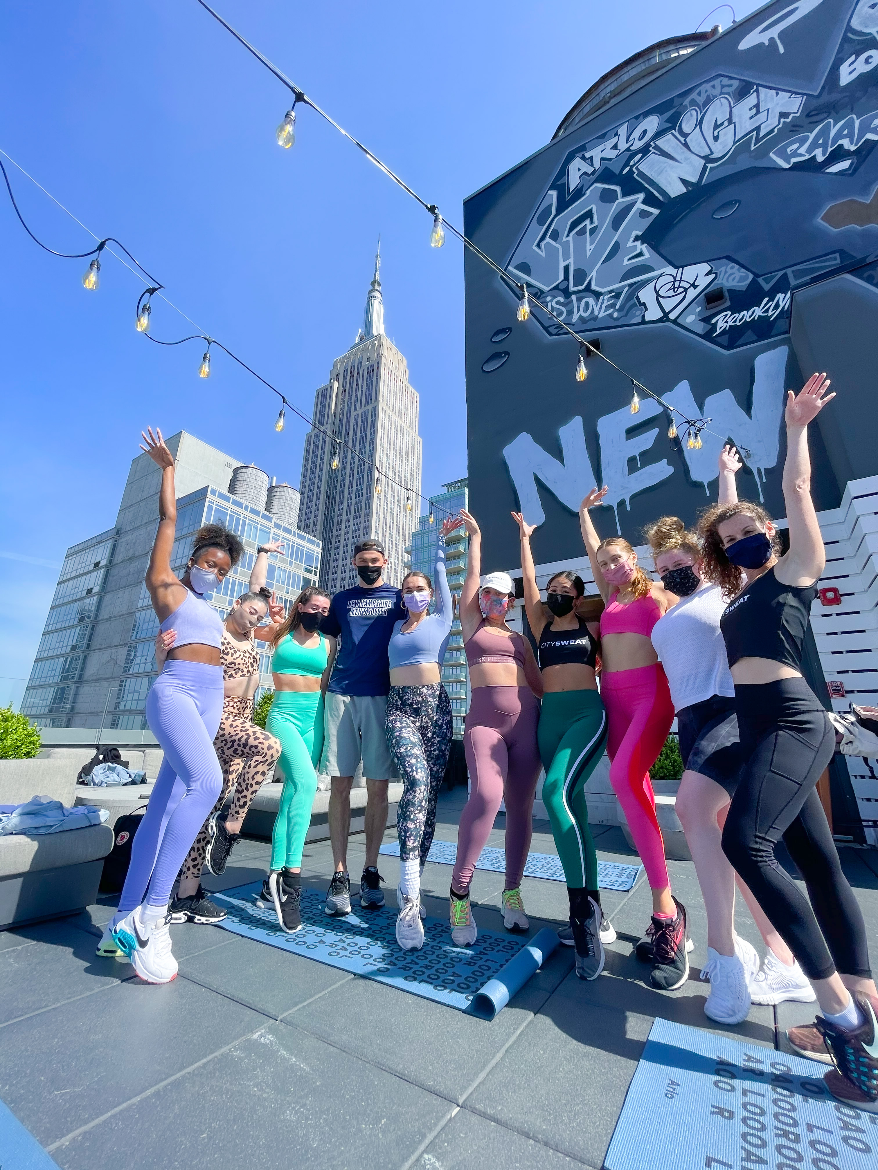Girls and guys in workout gear posing in front of black mural and empire state building on Arlo NoMad rooftop
