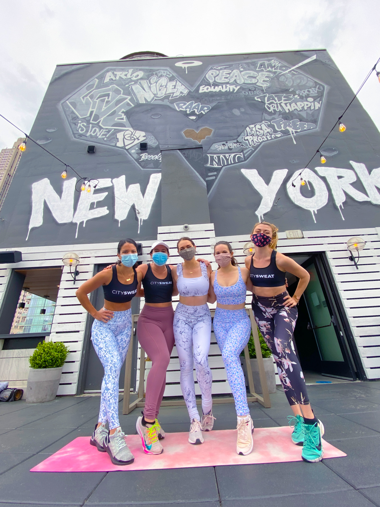 Girls in yoga workout gear standing together on pink yoga mat in front of black New York mural on Arlo NoMad rooftop