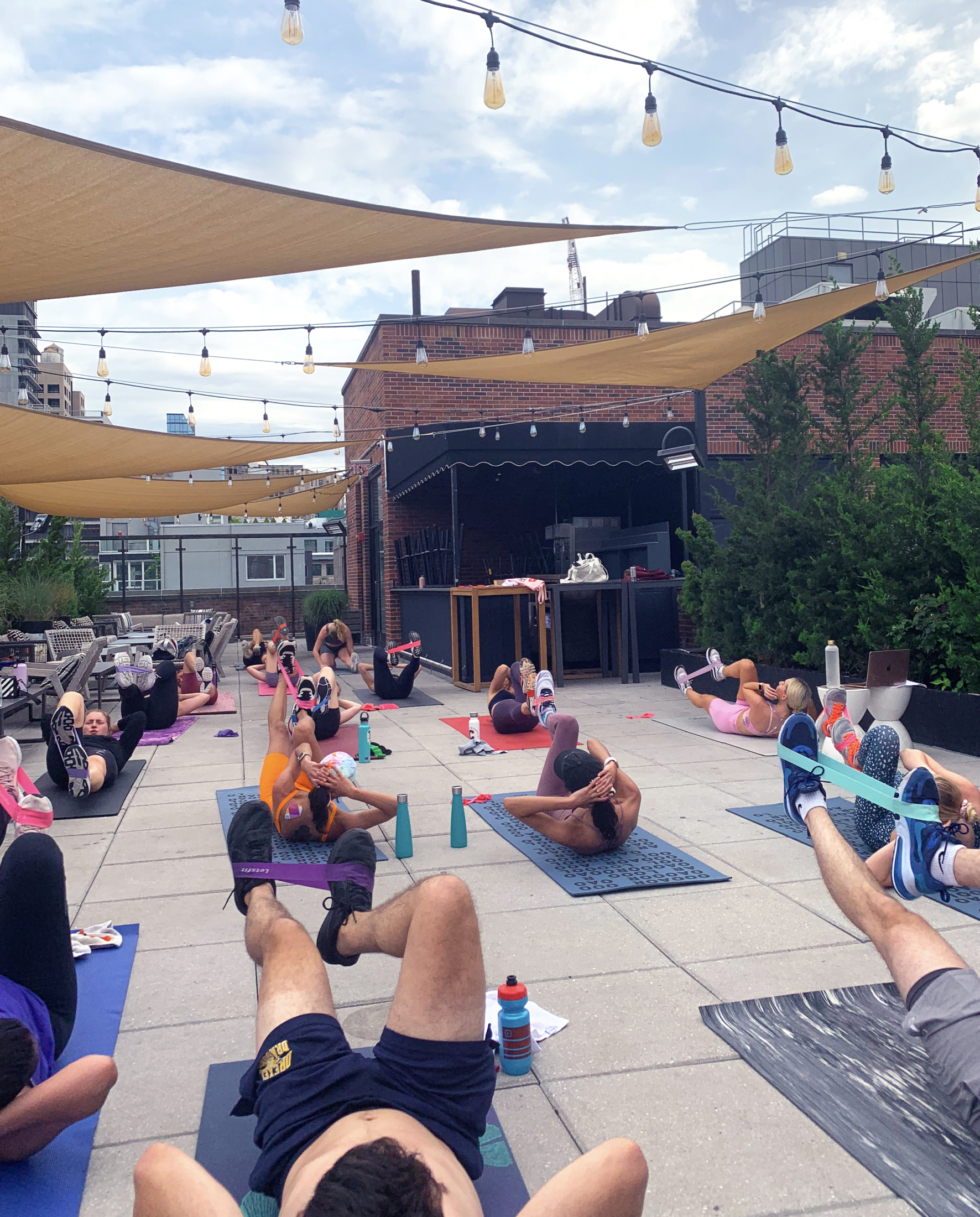 Arlo SoHo rooftop cardio sculpt class with guests on yoga mats lying on their backs working out