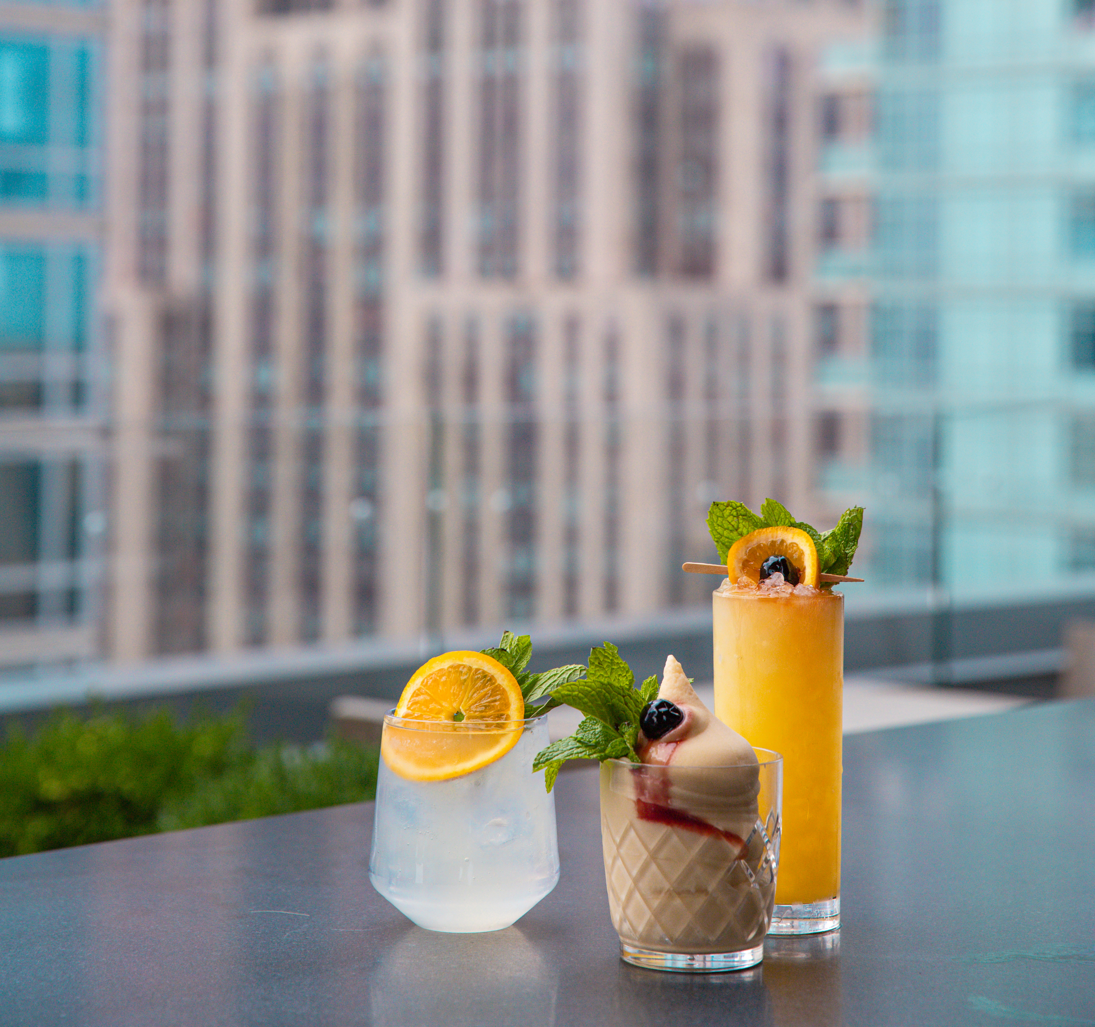 three cocktails on bar top outdoors at arlo nomad rooftop