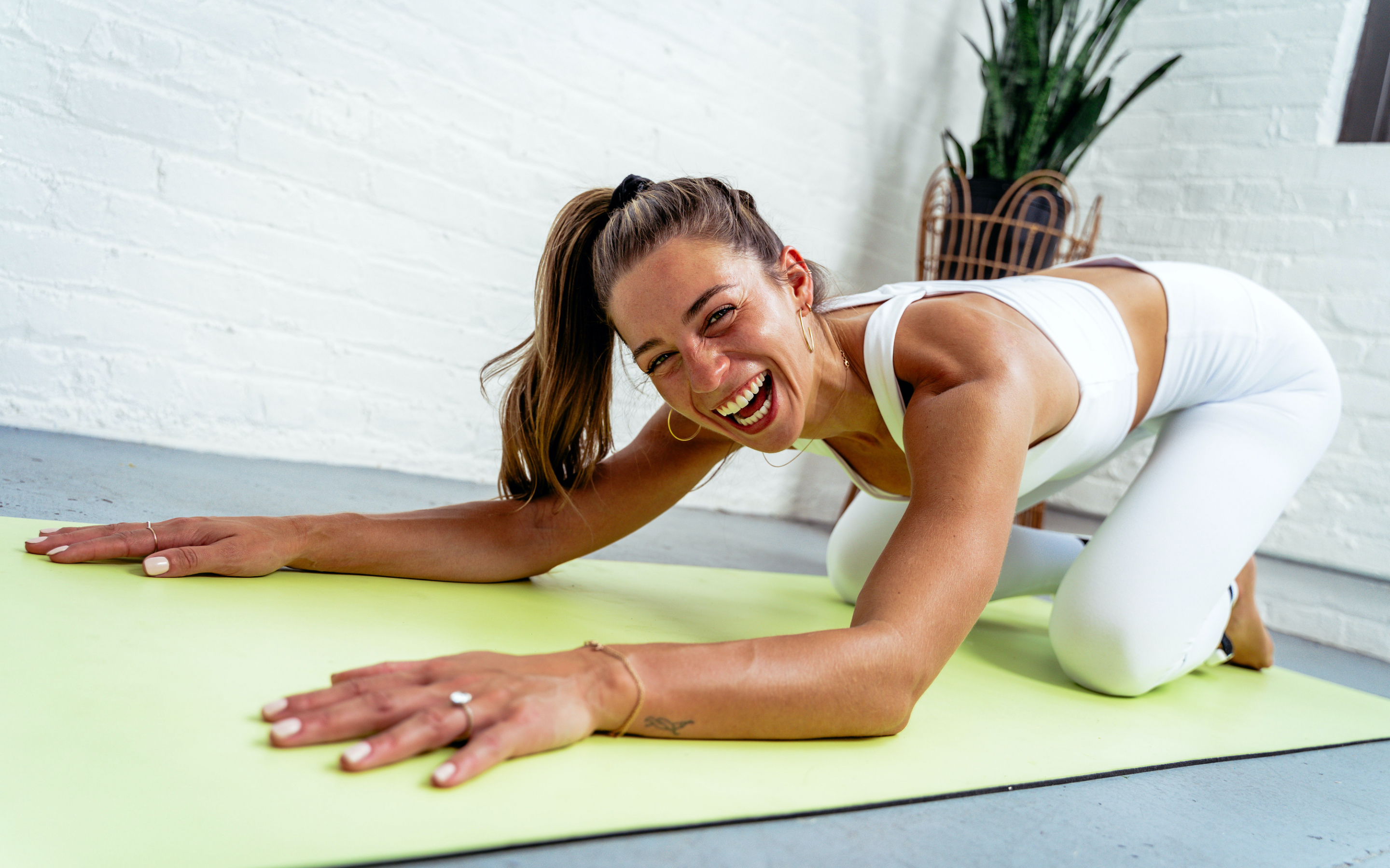 Girl in white yoga workout gear laughing and laying down on lime green yoga mat